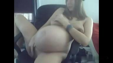 Une femme enceinte se touche devant sa webcam