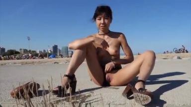 Mignonne asiatique se masturbe et gicle sur une plage fréquentée