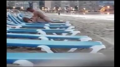 Un couple filmé par un voyeur baise sur une chaise longue de plage